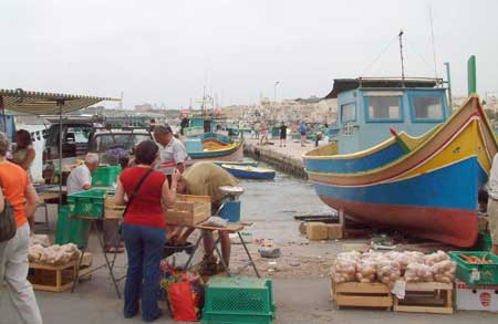 Shopping at the market in front of the harbour in Marsaxlook